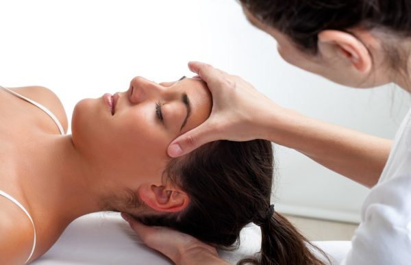 Therapist doing healing treatment on womans head.